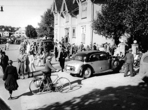 Bildet er trolig tatt på 1950-tallet og er tatt utenfor jernbanestasjonen. Det må ha vært en større anledning med «fine» gjester siden det står en staselig bil ved inngangen.