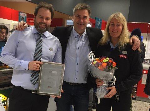 DIPLOM OG BLOMSTER: Butikksjef Aleksander Christoffersen (f.v.), distriktssjef Jørn Stensnes i Posten Norge og kasseleder Heidi Grimstvedt.