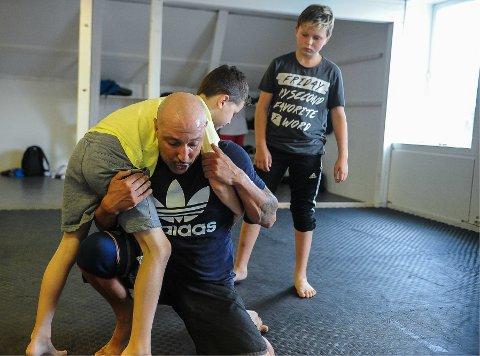 OLYMPISK BRYTING: Karim Rechaq viser bryteteknikker til Leon Numme (på ryggen) og Kristian Madsen. Marokkaneren håper den tradisjonsrike sporten vil slå an i Sandefjord.