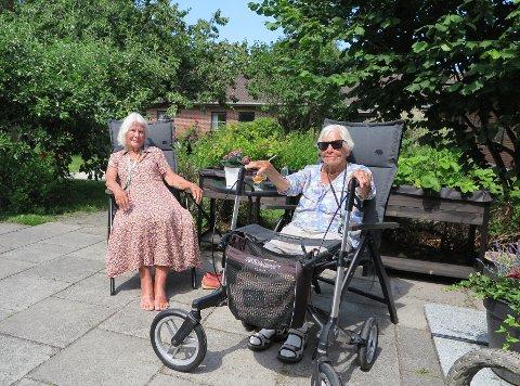 SPRUDLENDE DAMER: Kari og Wenche koser seg i hagen til Eik sykehjem.