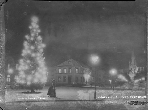 Det er stille på Torget julaften 1935. Juletreet står på sin faste plass utenfor Hornemannsgården. Nidarosdomen er opplyst. Det som ser ut som en av indremisjonens utskjærte trefigurer er gjerne en gutt som har stilt seg oppe på en innsamlingsbøsse. Ved siden av står en dame og ser på juletreet. Gården midt i bildet er Matzowgården, Munkegata 19, tidligere hotell og ølstue.