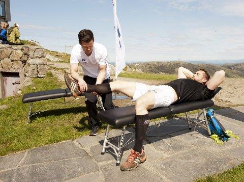 Thomas Vesteraas fikk krampe etter tre fjell. Han får hjelp av naprapat Joakim Marthinsen på toppen av det fjerde.