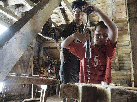 Jens Olav Steindal Halleraker (7) borer et hull i en liten treklosse som han skal bruke på båten sin. Båten lager han selv av en stor treklosse.