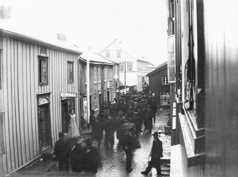 1. VELKJENT STRØK: Velkommen til Tiendebytte rundt 1910. Vi ser oppover i Sjøgata mot det som het Ulstadbua, og vi kjenner igjen både dagens Galleri Stokland og Kulturverkstedet. I døra til forretninga som selger både brød og tobakk står ei dame som ikke aner noen ting om den fæle murveggen som skal komme om en generasjons tid. Vi sparer henne for historien. 2. FOTOGRAF SOM TOK PLASS: Velkommen til Jacobsen og Elnans forretning i Sjøgata 22-24, omkring år 1900. Som vi ser er herrene ikke spesielt opptatt av handel, men av at de blir fotografert. Lukkertida er lang for å fange nok lys til et kornete, men historisk knips. 3. TIDSREISE: Vefsn museum forteller i sine notater at vi her ser Tankegården og Jacobsen og Elnans bakeri i Sjøgata. Men hva snakker folk om under sine hatter og skaut? Om det vil dessverre intet noen gang bli notert. 4. YRENDE LIV: Her er folk i Sjøgata rundt 1900. Vi ser Hellands frukthandel til høyre, opplyser Vefsn museum. Og det er vel den seinere Blomsterbua til venstre?