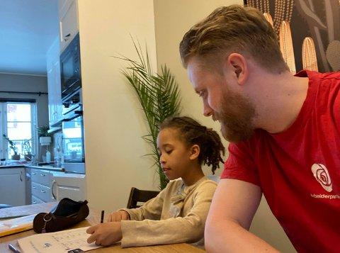 VELKJENT SITUASJON: Ordfører i Ullensaker, Eyvind Jørgensen Schumacher, har midlertidig flyttet seg fra rådhuset til kjøkkenbordet. Her hjelper han datteren med matematikkoppgaver.