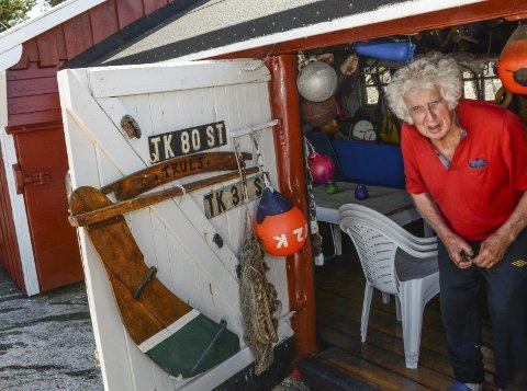 Alex Andersen står i døra til en av sjøbuene på eiendommen. På døra henger navskiltet til seilkoggen «Truls», som hans far kjøpte under krigen.