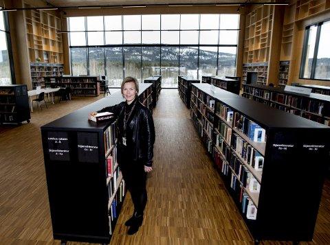Gode utsikter: Det meste ligger til rette for at biblioteksjef Ann Katrin Yri skal fortsette å begeistre og glede den som tar turen innom Nittedal bibliotek. Takhøyden ved vinduet er 7,5 meter, og Romeriksåsene fyller hele østveggen.Foto: Tom Gustavsen