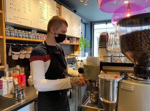 PÅ JOBB: Sentrumskaféen står på sparebluss, men lærling Ole André Kisen står fremdeles på jobb.