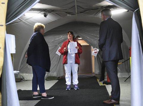 I MOTTAKET: Statsministeren fikk en titt inn i det provisoriske mottaket som ble rest med hjelp av telt fra Forsvaret. – Veldig fint at statsministeren tar seg tid til å besøke oss, sier sykepleier Christine Tonning. Direktør Eivind Hansen til høyre. FOTO: RUNE JOHANSEN