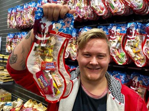 JUL: Butikkmedarbeider Daniel Kristoffersen viser fram julestrømpene som er i salg hos Europris på Brandbu.