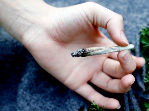 Hånd holder hasj-sigarett. Illustrasjonsfoto.