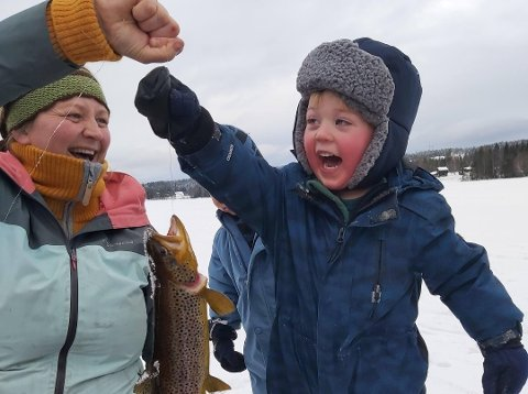Fiskelykke: Det ble en magisk opplevelse på isen for både ansatte og barn da de fikk opp denne ørreten fra Ulvenvannet med hjemmelagd fiskestang. Her er det Helene Isene og Fredrik Høvik som jubler over fangsten.