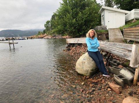 BEKYMRET: Anne Skinnemoen er redd for at det over 100 år gamle strandhuset kan rase ut i sjøen i vinter.
