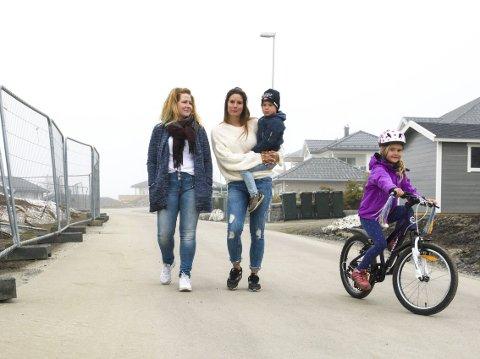 BLE NESTEN PÅKJØRT: Sjåføren måtte stå på bremsene da Felix Lindahl (5) veltet på sykkelen sin. Anette Lohne (t.v.) og Linn Kathrin Bjørnø forstår at det må bli en del trafikk til byggeplassene, men de vil at fartsgrensene skal overholdes. Gabriella Lindahl (6) på sykkel.