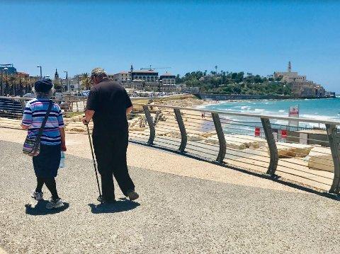 ROLIG LØRDAG: Det eldre ekteparet tilbringer sabbaten på strandpromenaden i Tel Aviv.  I bakgrunnen til høyre ses den historiske havnebyen Jaffa.
