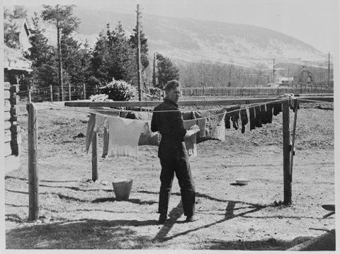 Norsk soldat forsøker å vaske litt på tunet til en liten fjellstue. (Original bildetekst)