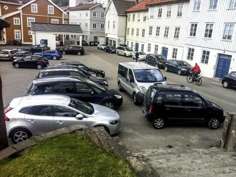 Parkering: På alle sider av Kirkehaugen sto bilene parkert. Også helt opp i dørene til husrekka langs Kirkegata.