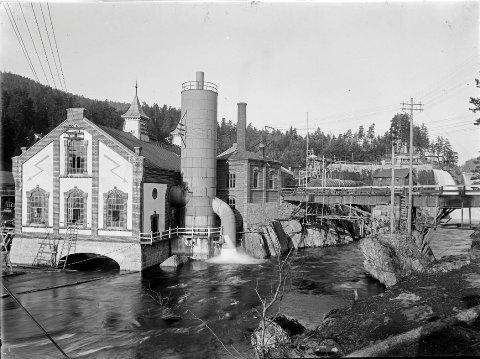 I kontoret til Tinfos papirfabrikk (midt i bildet) kan forhandlingene ha startet i februar 1904 om å leie strøm fra kraftverket Tinfos I (t.v.) til en forsøksfabrikk for gjødsel ved Heddalsvannet. (Foto: Tinfos/NIA).