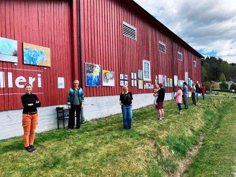 KORONATILPASSET: Jorunn Kjær, Cathrine Mustvedt og Annette Sollie stilte ut og solgte kunstverk lørdag. Bildene var hengt opp ute på låveveggen.  De besøkende holdt god avstand til hverandre.
