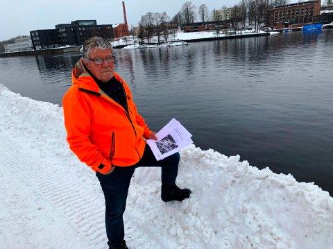 DYRERE: Vidar Krogsrud mener den ønskede gang- og sykkelbrua i Skien sentrum vil bli langt dyrere enn det overslaget viser.  Her står han der brua er planlagt, fra Jernbanebrygga over til Klosterøya.  I hånden har han to relevante rapporter.