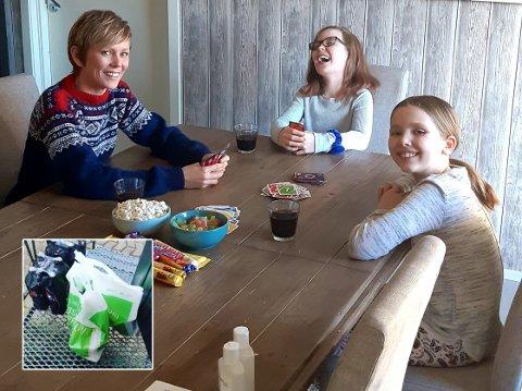 KORT OG GODT: Reidun Thorn Akre, Arielle Alice (9 år) og Hanna (8 år) koser seg inne med kortspill og lørdagsgodt til tross for karantene. Det litt ekstra takket være en god nabo som har hjulpet til med lørdagshandelen (innfelt bilde).