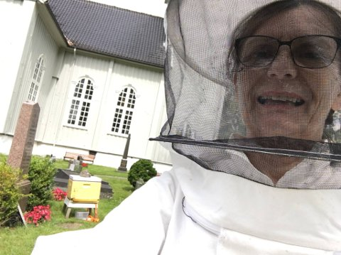 Ny bolig: Her, ved Drøbak kirke hadde bisvermen funnet ut at de ville bo. Irene Andrem tok på seg en tett bidrakt med hatt og slør, som hun alltid bruker når hun steller biene. Det gjorde svermen på kirkegården roligere. FOTO: Privat