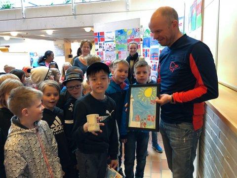 Fikk premie: Sigurd Solvang har tenget framsida på årets 17. maiprogram på Tynset og fikk tegningen rammet inn og en kopp av lederi 17.maikomiteen Jan Roger Olsson.