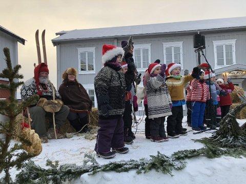 Stenbråttet Barnehage synger og nissen og nissemor har tatt plass på snøscena under åpningen av julemarkedet 2018.