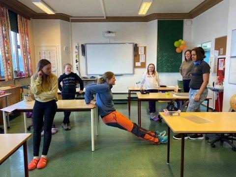 Fysioterapeut Tove Hegseth viser elevene en av øvelsene.