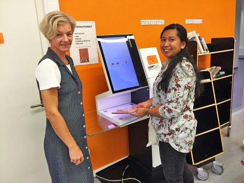 Biblioteksjef Marianne Selvik viser lånekunde Safiera Prilia fra Vinterbro hvordan hun kan låne bøker utenfor den bemannede åpningstiden.