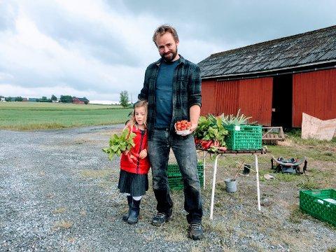 Morten Jerven(t.h) driver Linnestad Gård. Her viser han og Robin frem noe av det man kunne få kjøpt utenfor gårdsbutikken søndag, nemlig redikker og jordbær.