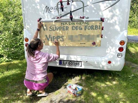Her blir det spøkefulle skiltet klargjort og hengt opp bak på bobilen. – Vi ønsker å bidra til at trafikken flyter litt bedre, sier bilturist Karina Wien fra Bergen.