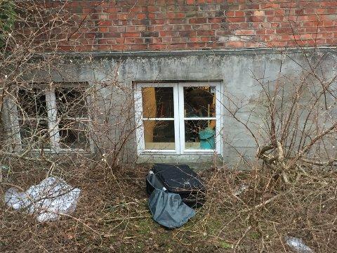 UNDERSØKER: En politibetjent undersøker åstedet innenfor vinduet der tyvene tok seg inn tidlig tirsdag morgen.