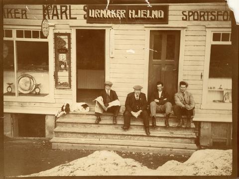 Den tidligere butikken til urmaker og sportsforhandler Karl Sivertzen er overtatt av urmaker Hjelmo i mellomkrigstiden. På trappa fra v: Peder Tangen, urmaker Hjelmo, Sigvart Sættem og Osvald Knutsen.