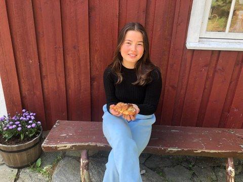 Inger Søndeled (14) med en av de populære kanelsnurrene som selges på Søndeled gårdsbakeri.