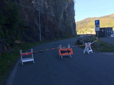 Steinblokken som raste ned ligger bak sperringen, til venstre. Det er fredag morgen omkjøring via deler av bobilparkeringen. Foto: Erik Thime