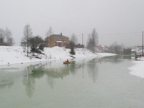 PÅ BÅTTUR: Isproppen i elva har gitt mye overvann på marken ved siden av. Her var det noen unger som fant frem gummibåten og tok seg en båttur.