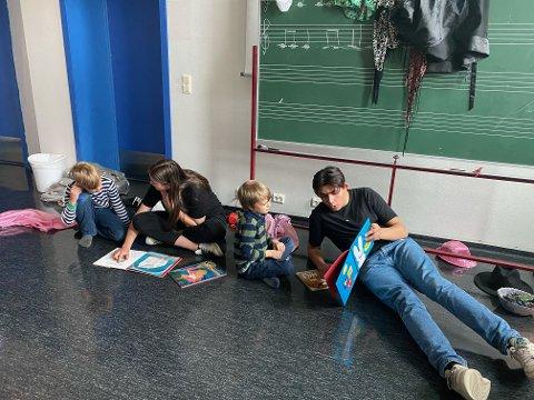 HØYTLESNING: VGS-elevene leser høyt, mens SFO-barna koser seg.