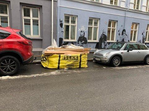 Her kan man se en avfallssekk som er plassert mellom to biler som står parkert. Foto: Privat