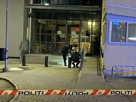 Politiets krimteknikere jobber utenfor inngangen til Stovner politistasjon lørdag kveld. Det ser ut til å være brannskader vtil høyre for inngangsdøren.