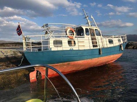 VENTAR: Slik ligg båten og ventar på flod sjø. Den skal ikkje ha fått skader på skroget.