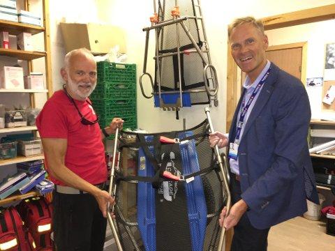 Øystein Nystad i Bodø Røde Kors og banksjef Per Martin Olsen i SpareBank1 sammen med den nye hjulbåren som skal hjelpe skadde i marka.