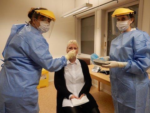 Test-team: Sykepleierne Trude Zahlsen, Gunnbjørg Olufsen og Nine Therese Hansen opplever jobben de gjør under situasjonen med korona som meningsfull og givende. Her er de utstyrt for utendørs testing med frakk, munnbind og visir.