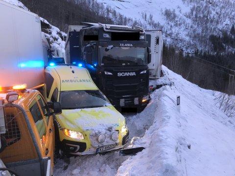 DRAMATISK: Her står ambulansen i klem mellom vogntoget som skled på isen og bergningsbilen. Avisa Nordland har fjernet kjennetegnene til vogntoget.