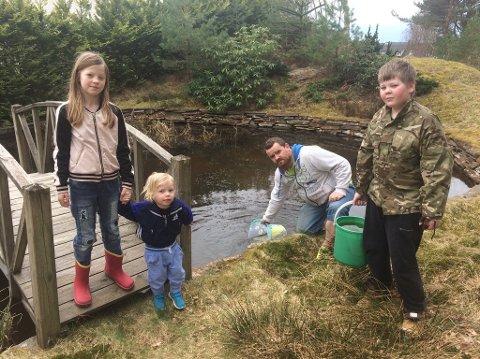 Lotte (10, f.v.), Aron (2), Kjell Ahlsen (39) og Sebastian (13) måtte hente vann fra dammen da vannet forsvant i huset.