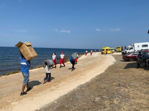 Migrantene går i stekende varme mens de flytter seg inn på den nye leiren, etter at Moria-leiren i Lesvos brente ned i forrige uke.