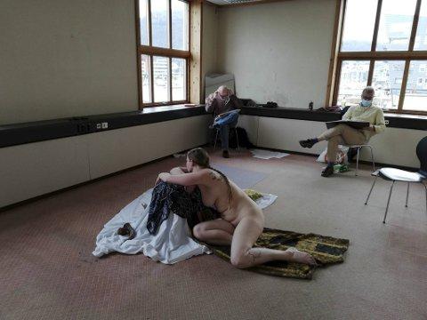Tove Hassel ligger lett henslengt på gulvet mens tilskuerne tegner intenst.
