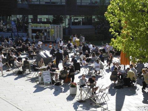 Folk ser ut til å nyte både sol og koronalettelser denne fredags ettermiddagen på Cornerteateret.