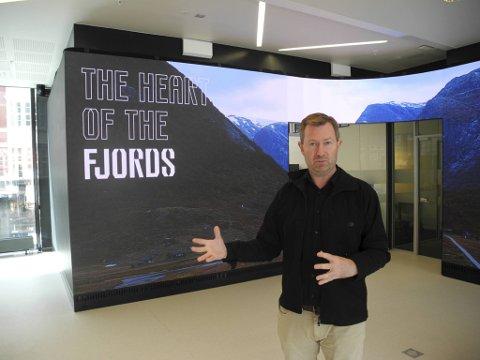 Reiselivsdirektør Anders Nyland foran en av de nye tingene som er på plass i turistinformasjonen, en 30 kvadratmeter stor skjerm.