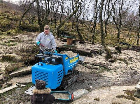 Her legger Krister og Tobias (1,5) Høie på skjellsand for å styrke jord og eng i parken.